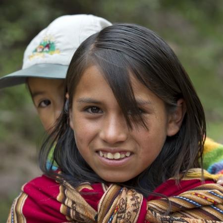 cusco region: Chica dando a cuestas a su hermana, sonriente, Valle Sagrado, Cusco, Per�