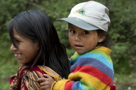 Girl giving piggyback to her sister and smiling, Sacred Valley, Cusco Region, Peru