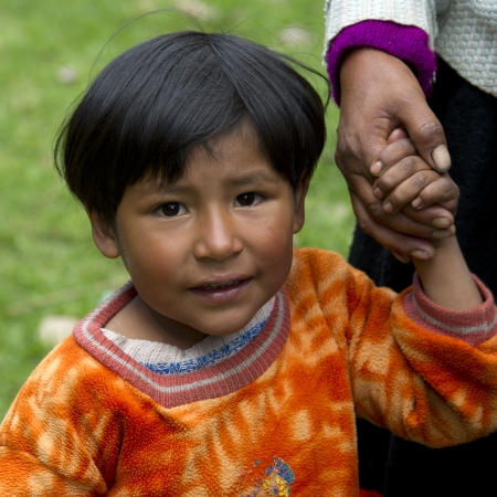 Portrait of a girl holding her mother's hand, Sacred Valley, Cusco Region, Peru