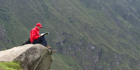 Person reading a book at the edge of a rock at The Lost City of The Incas, Machu Picchu, Cusco Region, Peru