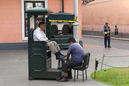 lima: Man having shoes polished in shoe polish booth, Historic Centre of Lima, Lima, Peru
