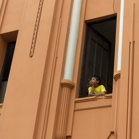 curiousness: Boy looking through the window of a building in Historic Centre of Lima, Lima, Peru Editorial
