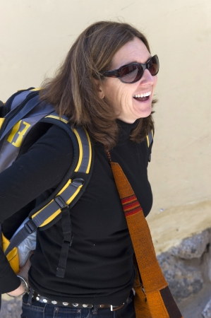 blissfully: Woman carrying backpack and smiling, Barrio de San Blas, Cuzco, Peru