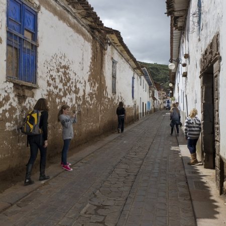 full disclosure: Girl taking picture of her sister in a street of Barrio de San Blas, Cuzco, Peru Editorial
