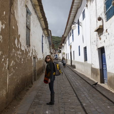 Woman carrying backpack and standing in a street of Barrio de San Blas, Cuzco, Peru