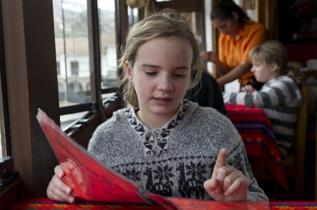 Girl reading menu in a restaurant, Cuzco, Peru