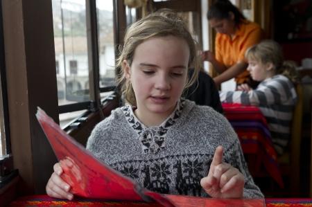 freetime activity: Girl reading menu in a restaurant, Cuzco, Peru