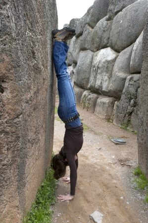 Woman doing a handstand in a narrow alley, Sacsayhuaman, Sacred Valley, Cusco Region, Peru photo