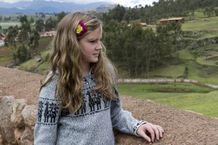 cusco region: Chica de pie en el techo y mirando al horizonte, Chinchero, Valle Sagrado, Regi�n Cusco, Per� Editorial