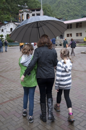sheltering: Mother with her daughters sheltering under an umbrella, Peru