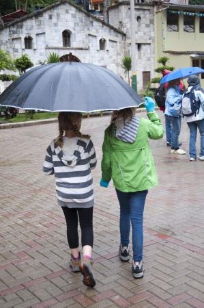 sheltering: Girls sheltering under an umbrella, Peru