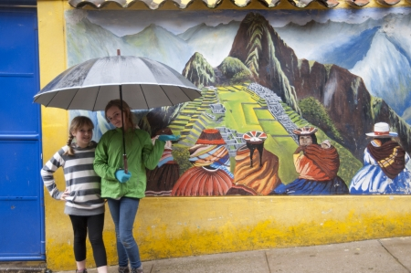 Girls sheltering under an umbrella in front of a mural of Machu Picchu, Cusco Region, Peru