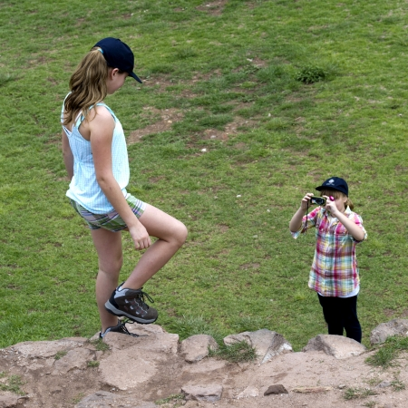cusco region: Girl taking picture of her friend with a camera at Incan terraces, Moray, Machu Picchu, Cusco Region, Peru