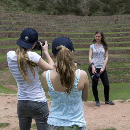 Teenage girl taking picture of her friend with a camera at Incan terraces, Moray, Machu Picchu, Cusco Region, Peru