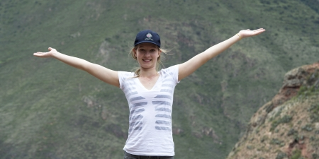 Teenage girl with her arm outstretched with Sacred Valley in the background, Cusco Region, Peru Stock Photo - 17227759