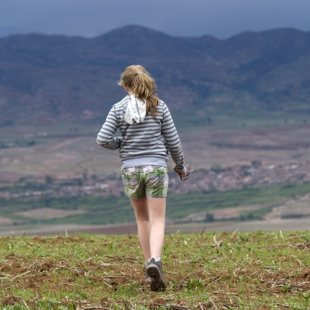 getting away from it all: Teenage girl walking in a field with Sacred Valley in the background, Cusco Region, Peru