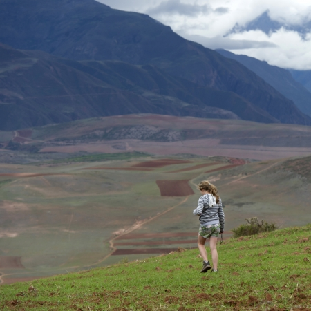 Teenage girl walking in a field with Sacred Valley in the background, Cusco Region, Peru