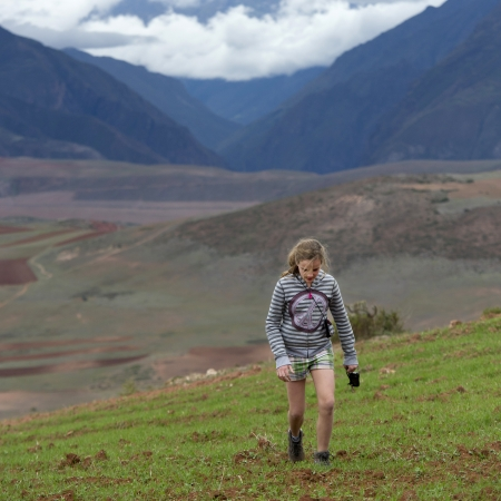Teenage girl walking in a field with Sacred Valley in the background, Cusco Region, Peru Stock Photo - 17227827