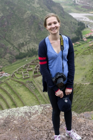 Teenage girl smiling with Archaeological Park of Pisac in the background, Pisac, Sacred Valley, Cusco Region, Peru