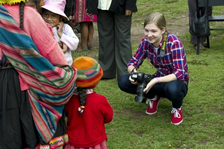 peruvian culture: Tourist taking picture of Quechua Indian people, Chumpepoke Primary School, Poques, Sacred Valley, Cusco Region, Peru
