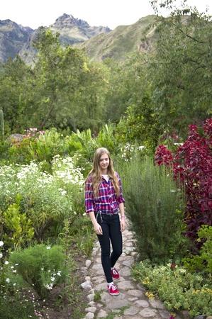 sacred valley of the incas: Teenage girl walking in the garden of Willka Tika Guesthouse, Willka Tika, Sacred Valley, Cusco Region, Peru Editorial