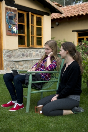 Sisters looking at a laptop in the lawn of Willka Tika Guesthouse, Willka Tika, Sacred Valley, Cusco Region, Peru Stock Photo - 17227912