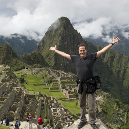 Man with his arm outstretched at The Lost City of The Incas, Machu Picchu, Cusco Region, Peru