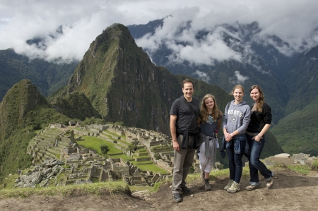 Man with his family with The Lost City of The Incas in the background, Machu Picchu, Cusco Region, Peru