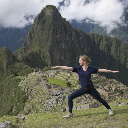 Teenage girl doing warrior 2 pose with The Lost City of The Incas in the background, Machu Picchu, Cusco Region, Peru