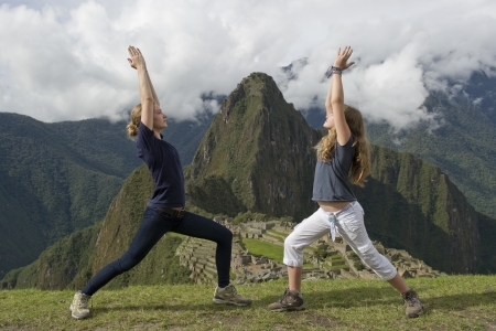 top: Teenage girls doing warrior 1 pose with The Lost City of The Incas in the background, Machu Picchu, Cusco Region, Peru