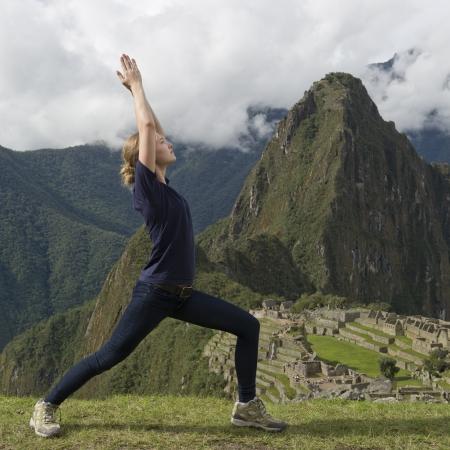 cusco region: Adolescente haciendo una pose del guerrero con la ciudad perdida de los Incas en el fondo, Machu Picchu, Cusco, Per�