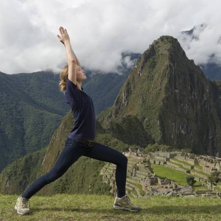 Teenage girl doing Warrior 1 pose with The Lost City of The Incas in the background, Machu Picchu, Cusco Region, Peru