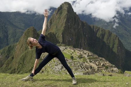 cusco region: Teenage girl doing triangle pose with The Lost City of The Incas in the background, Machu Picchu, Cusco Region, Peru