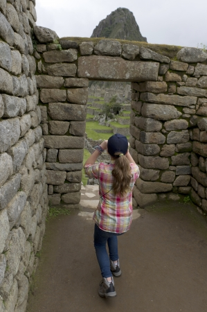 Girl photographing at The Lost City of The Incas, Machu Picchu, Cusco Region, Peru photo