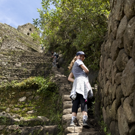 Teenage girl standing on steps at The Lost City of The Incas, Machu Picchu, Cusco Region, Peru