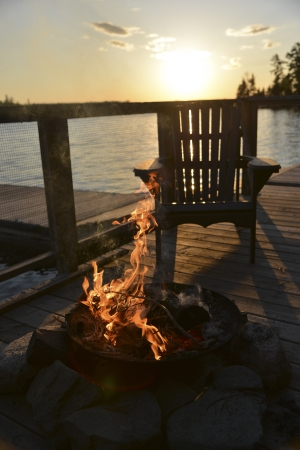 adirondack chair: Adirondack chair and campfire on a dock, Lake of The Woods, Keewatin, Ontario, Canada