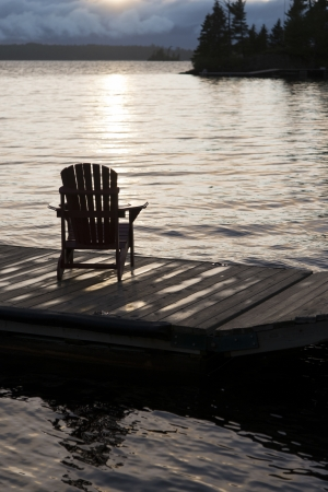 adirondack chair: Adirondack chair on a dock at the Lake of The Woods, Keewatin, Ontario, Canada