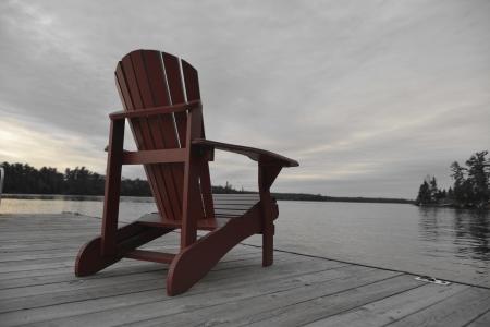 adirondack chair: Adirondack chair on a deck at lake, Lake Of The Woods, Keewatin, Ontario, Canada