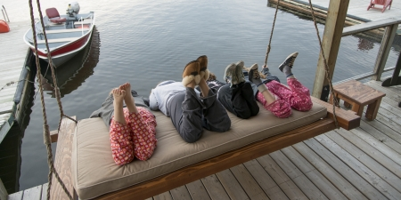 Three girls enjoying on swing chair at a dock, Lake Of The Woods, Keewatin, Ontario, Canada