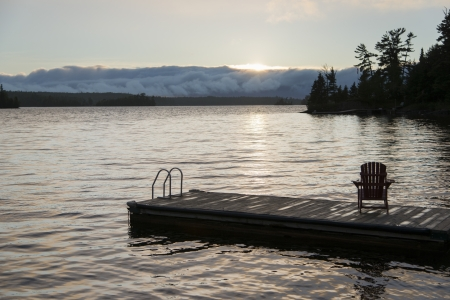 adirondack chair: Adirondack chair on dock at lake, Lake Of The Woods, Keewatin, Ontario, Canada