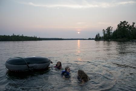 3 人の女の子が森の中、カナダのオンタリオ州キーウェティン ゴムボートの湖と湖で楽しんで 写真素材