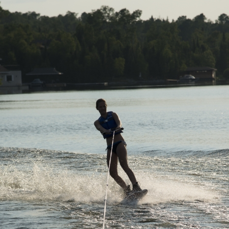 wakeboarding: Woman waterskiing in a lake, Lake of The Woods, Keewatin, Ontario, Canada