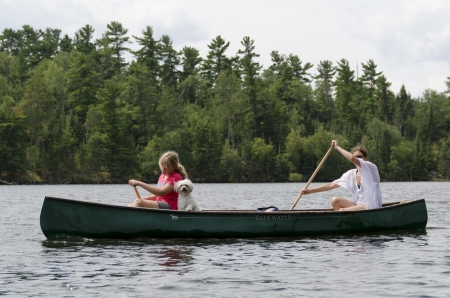 Woman rowing a boat with her daughter, Lake of The Woods, Keewatin, Ontario, Canada