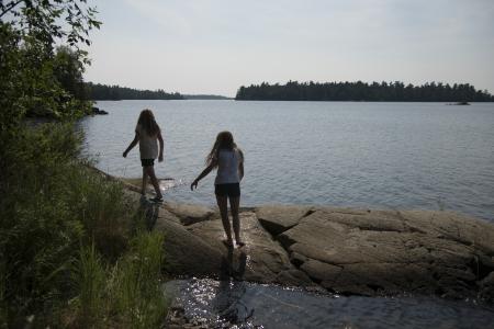 unorganized: Girls walking on the rocks at the lakeside, Lake of The Woods, Kenora, Unorganized Kenora, Ontario, Canada Stock Photo