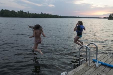 Girls jumping into a lake, Lake of The Woods, Keewatin, Ontario, Canada photo