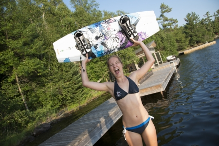 wakeboarding: Woman holding a wakeboard and looking excited at the lakeside, Lake of The Woods, Keewatin, Ontario, Canada