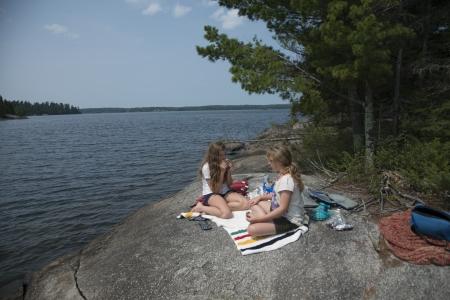 Girls sitting on the rock at the lakeside, Lake of The Woods, Kenora, Unorganized Kenora, Ontario, Canada
