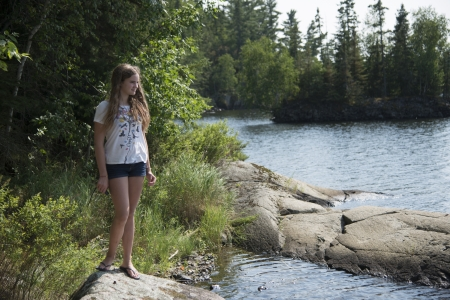 tween: Girl standing on a rock at the lakeside, Lake of The Woods, Keewatin, Ontario, Canada
