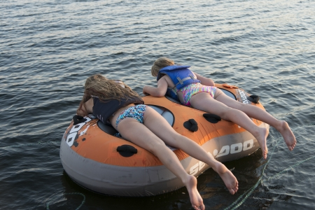 Two girls lying on an inflatable raft floating on water, Lake of The Woods, Ontario, Canada Stock Photo - 23272799