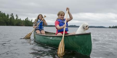 piragua: Dos chicas remar en un bote en un lago, el lago de los bosques, Ontario, Canadá